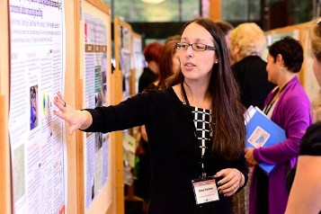 Diana Rohlman pointing at her poster