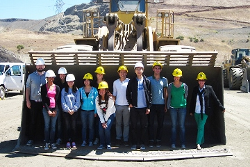 Students standing next to heavy equipment
